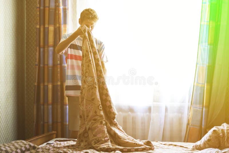 Homem adulto que faz uma cama, conceito f do serviço de sala do hotel foto de stock royalty free