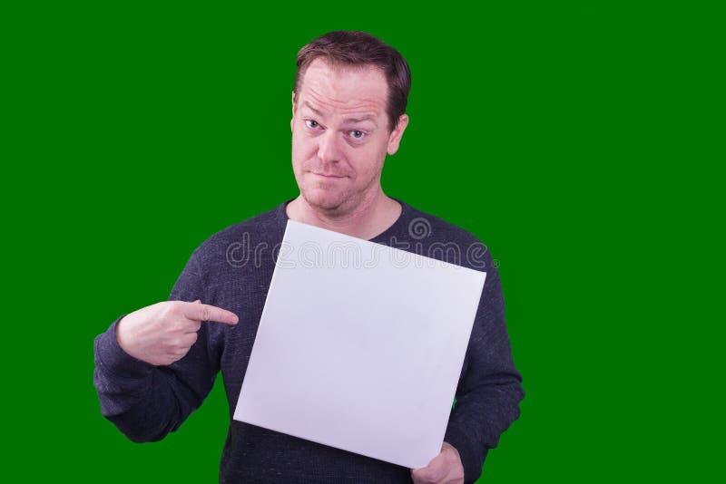 Homem adulto que guarda o sinal branco vazio que aponta um dedo no sinal que aumenta as sobrancelhas fotos de stock royalty free