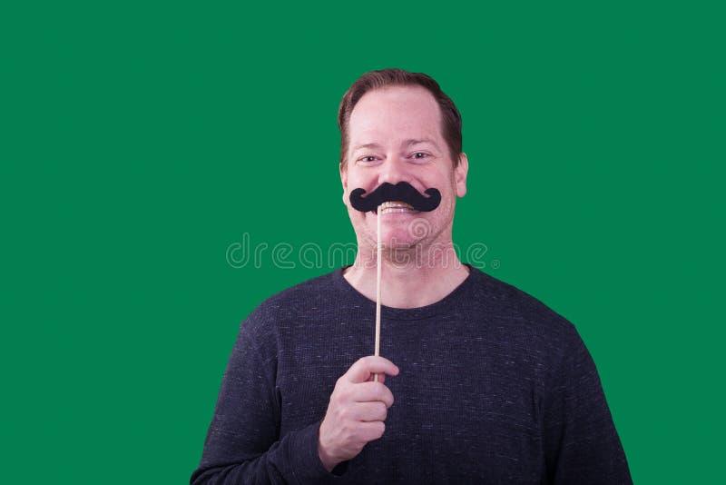 Homem adulto que mantém o bigode falsificado para enfrentar o sorriso no contexto verde da tela imagens de stock