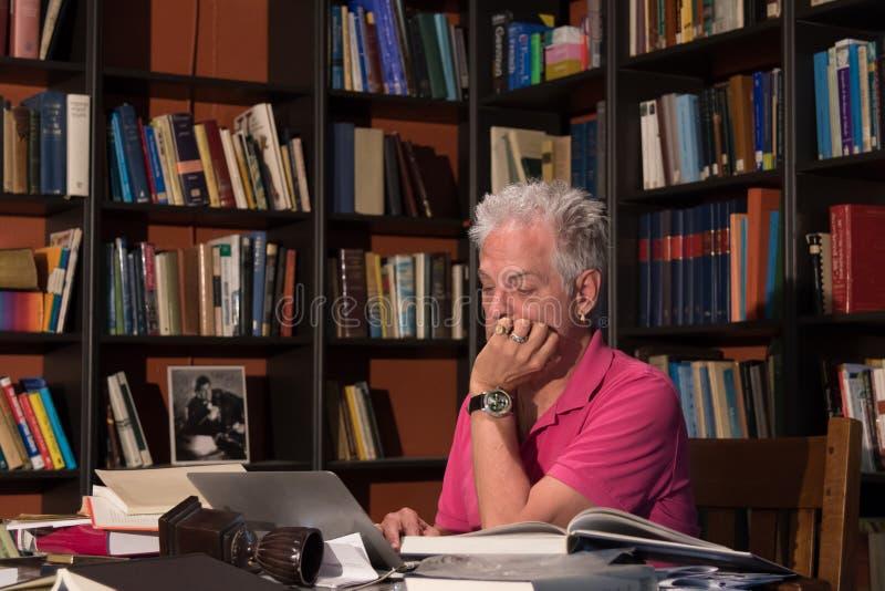 Homem adulto que senta-se na mesa que olha o portátil imagens de stock