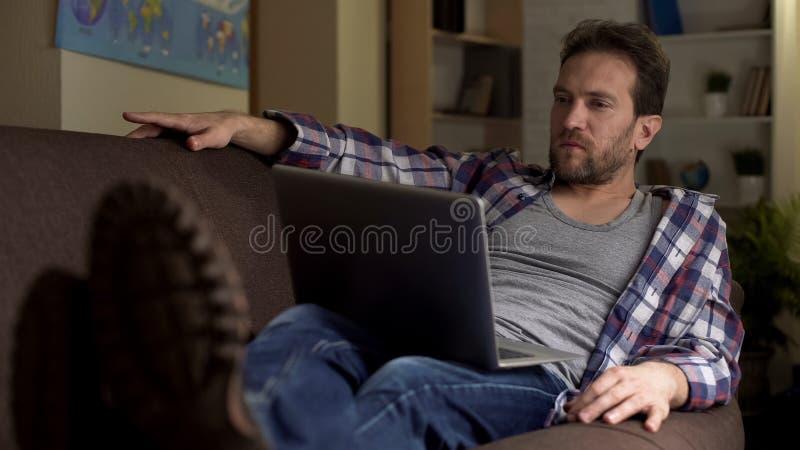 Homem adulto que senta-se no sofá com o computador no regaço que pensa, planos futuros, escolha foto de stock