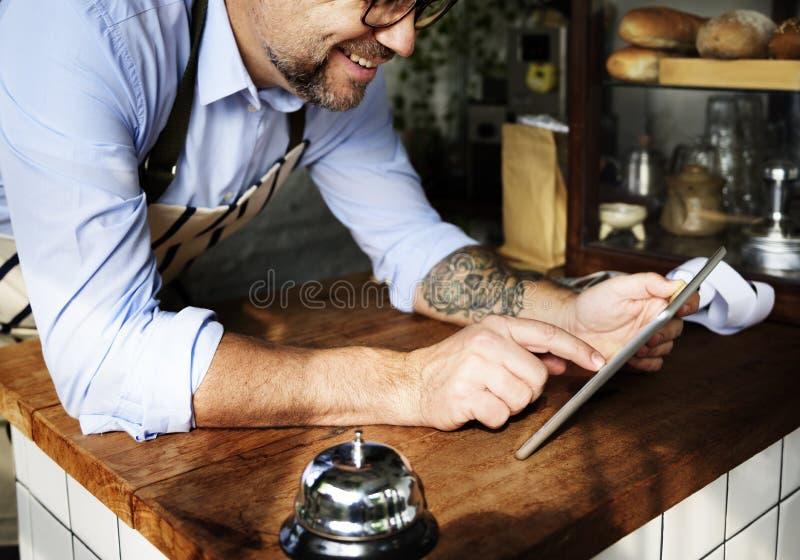 Homem adulto que usa a tabuleta na loja da padaria fotos de stock royalty free
