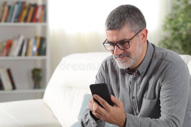 Homem adulto que usa um telefone esperto em casa foto de stock