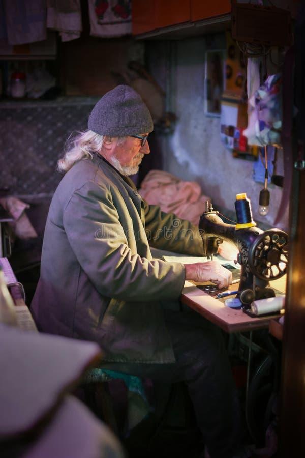 Homem adulto superior com máquina de costura fotos de stock royalty free