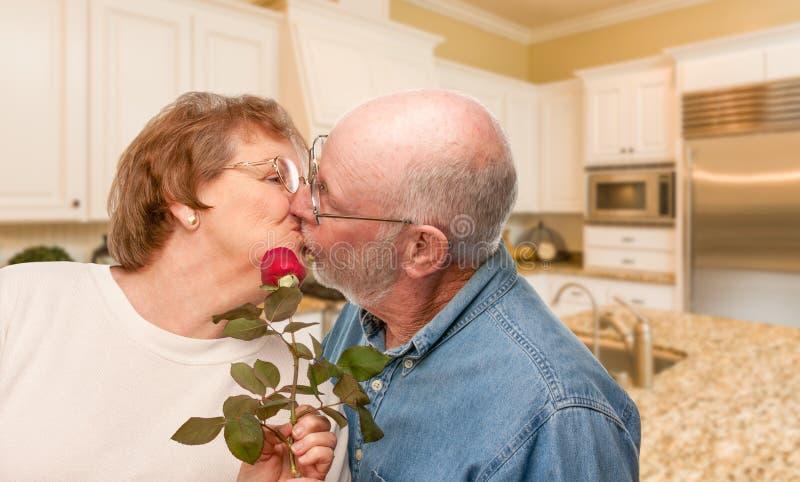 Homem adulto superior feliz que dá Rosa vermelha a sua esposa em uma cozinha imagem de stock royalty free