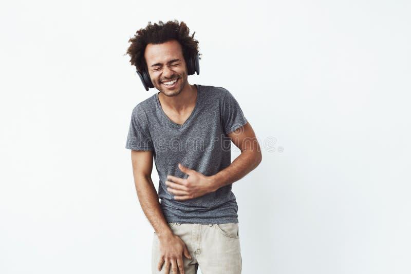 Homem africano alegre nos fones de ouvido que ri sobre o fundo branco Olhos fechados foto de stock royalty free
