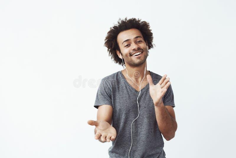Homem africano alegre que escuta a música nos fones de ouvido que dançam o canto fotos de stock royalty free