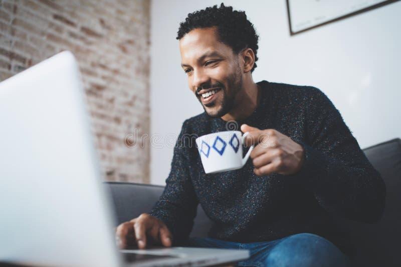 Homem africano alegre que usa o computador e sorrindo ao sentar-se no sofá Indivíduo preto que mantém o copo cerâmico disponivel  imagens de stock