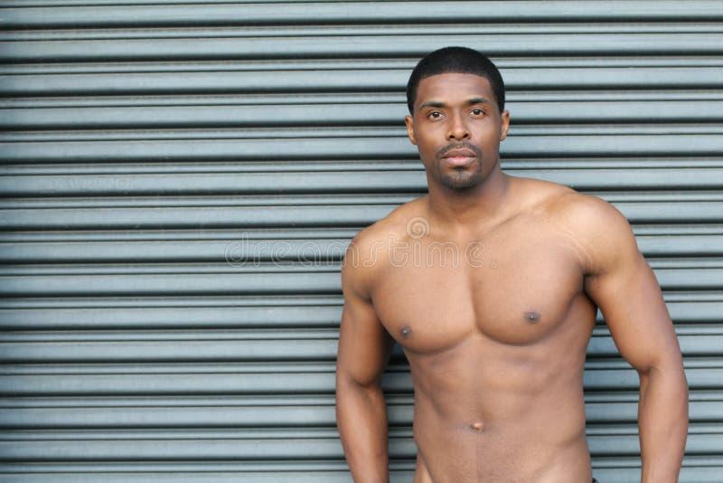 Homem africano bonito despido molhado 'sexy' novo muscular que levanta nos troncos com espaço da cópia fotografia de stock royalty free