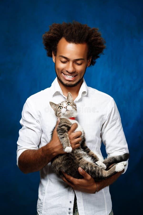 Homem africano considerável novo que guarda o gato sobre o fundo azul fotografia de stock royalty free
