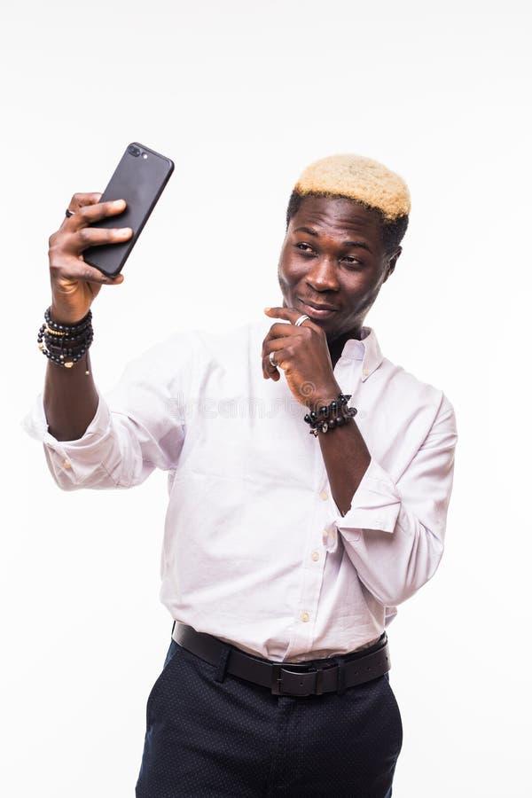 Homem africano considerável novo que toma um selfie com um telefone celular, isolado no branco imagens de stock