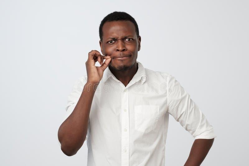 Homem africano considerável que mostra um sinal da boca de fechamento imagem de stock