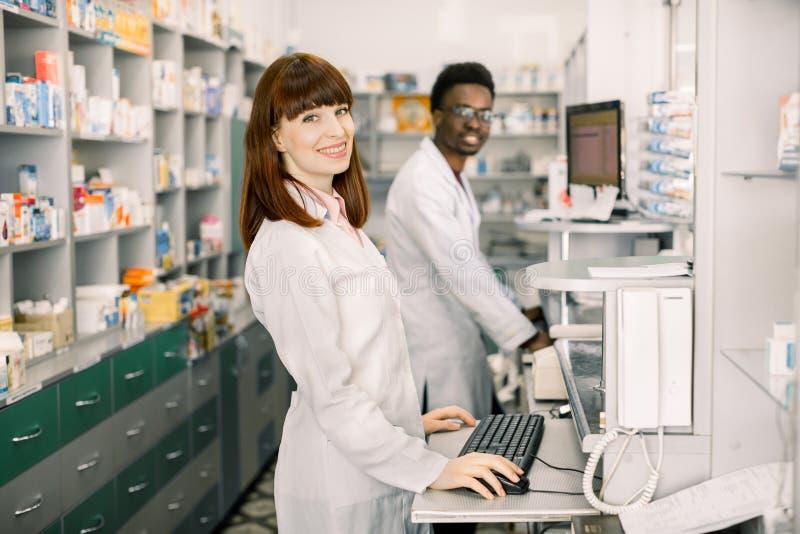 Homem africano de dois farmacêuticos alegres novos e mulher caucasiano que trabalham junto e que usam computadores pharmacists imagem de stock royalty free