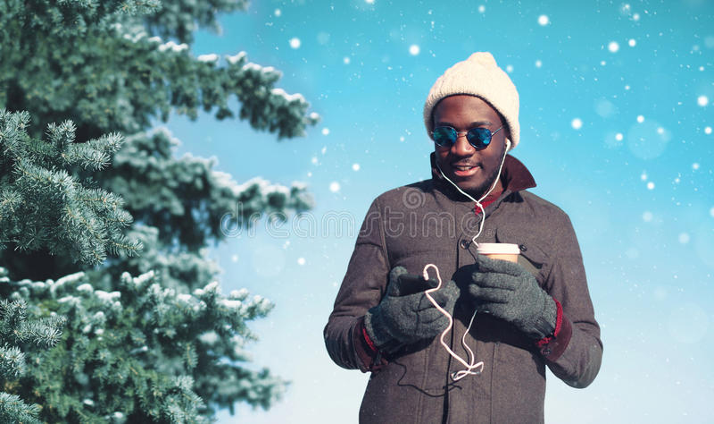Homem africano de sorriso dos jovens do inverno que aprecia a música de escuta no smartphone com a xícara de café de papel sobre  imagem de stock royalty free