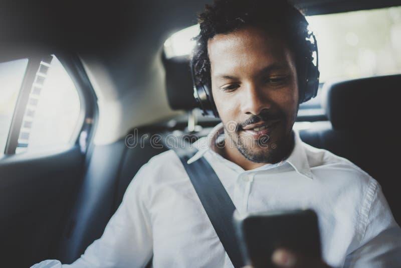 Homem africano de sorriso dos jovens que usa o smartphone ao sentar-se no assento traseiro no carro do táxi Conceito dos executiv foto de stock royalty free