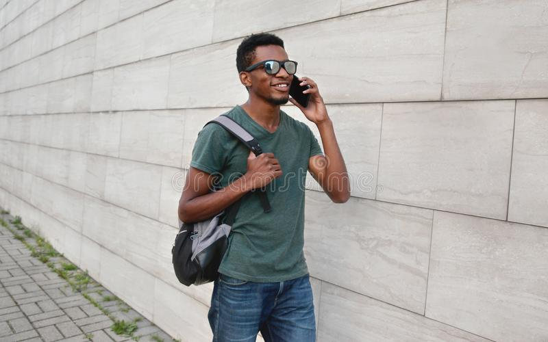 Homem africano de sorriso feliz do retrato que chama o smartphone que anda com a trouxa na rua da cidade sobre a parede de tijolo imagens de stock