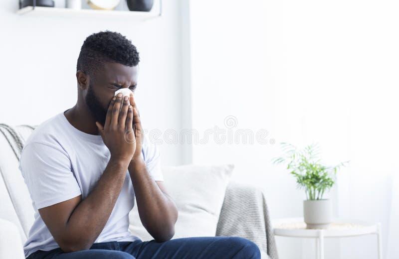 Homem africano doente novo que limpa o nariz descarado imagem de stock royalty free