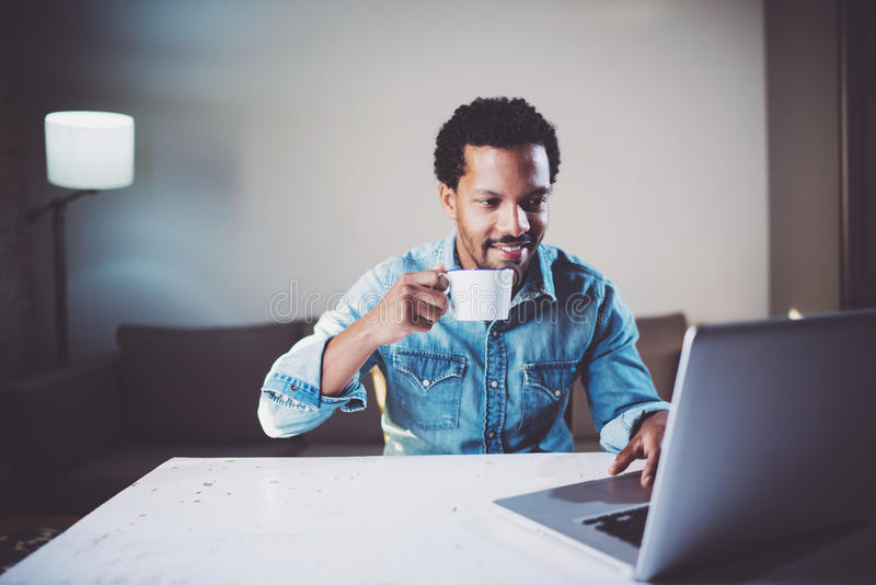 Homem africano farpado de sorriso que faz a conversação video através do portátil com sócios ao guardar o chá preto do copo branc fotografia de stock