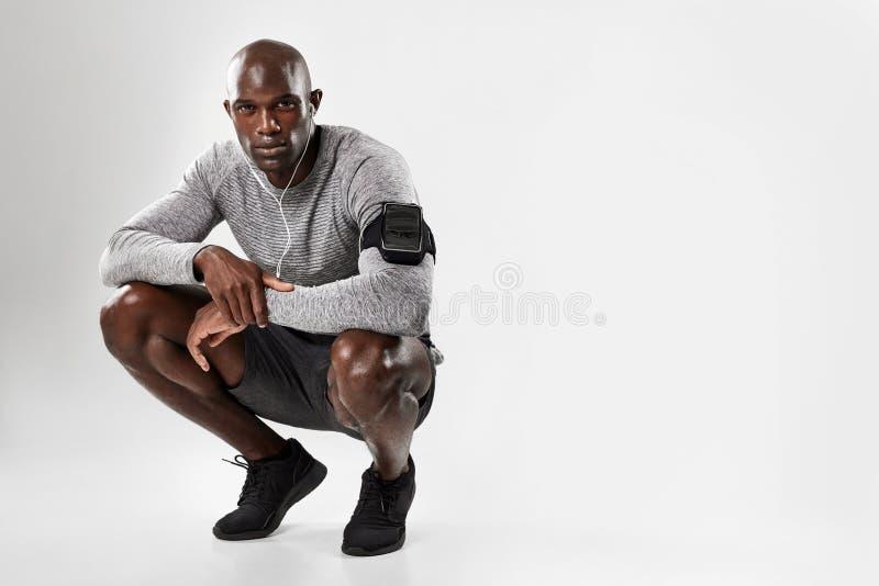 Homem africano novo apto que agacha-se sobre o fundo cinzento imagem de stock