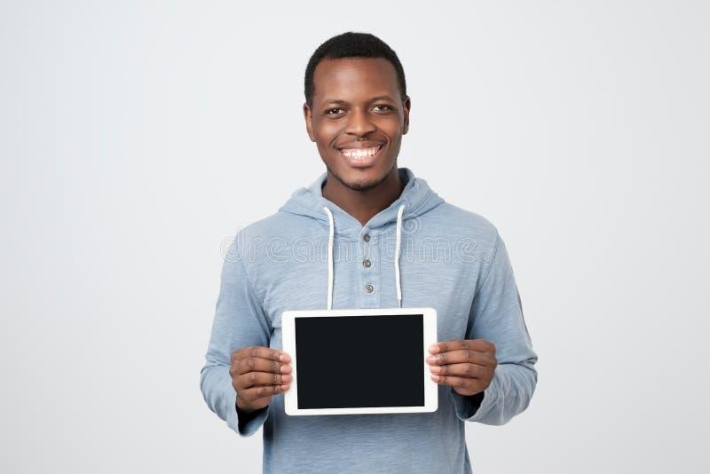 Homem africano novo com a tela da exibição da tabuleta da tabuleta moderna fotos de stock royalty free