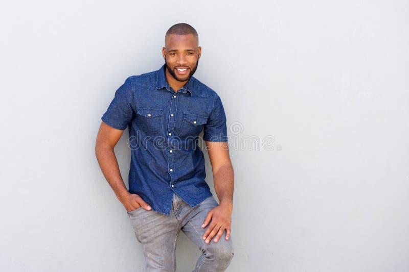 Homem africano novo considerável que levanta contra a parede cinzenta fotos de stock royalty free