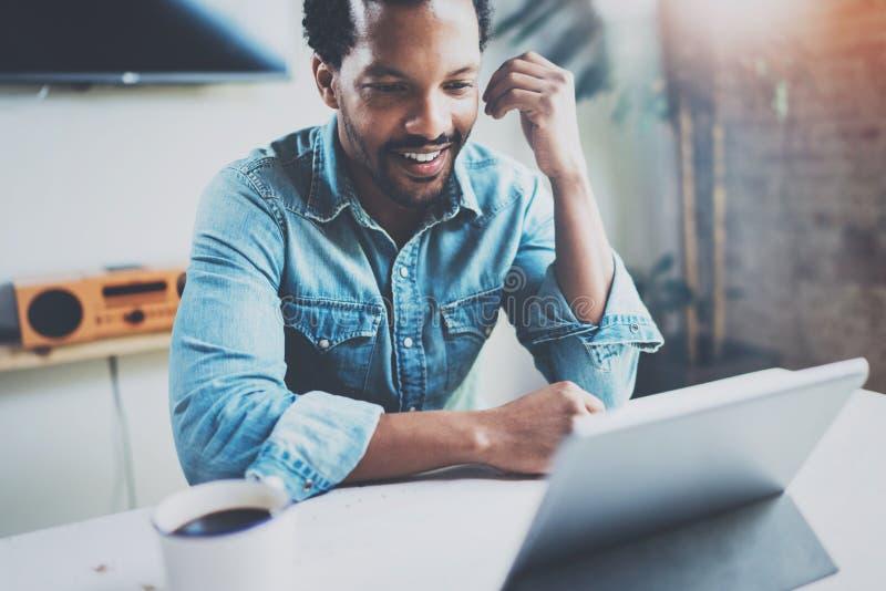 Homem africano novo de sorriso que faz a conversação video através da tabuleta digital com sócios comerciais ao beber o preto foto de stock