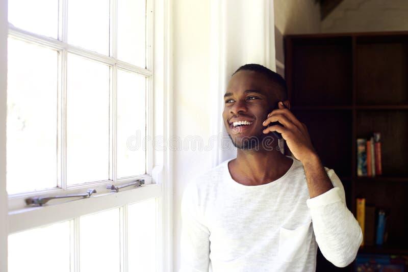 Homem africano novo em casa que faz um telefonema fotografia de stock