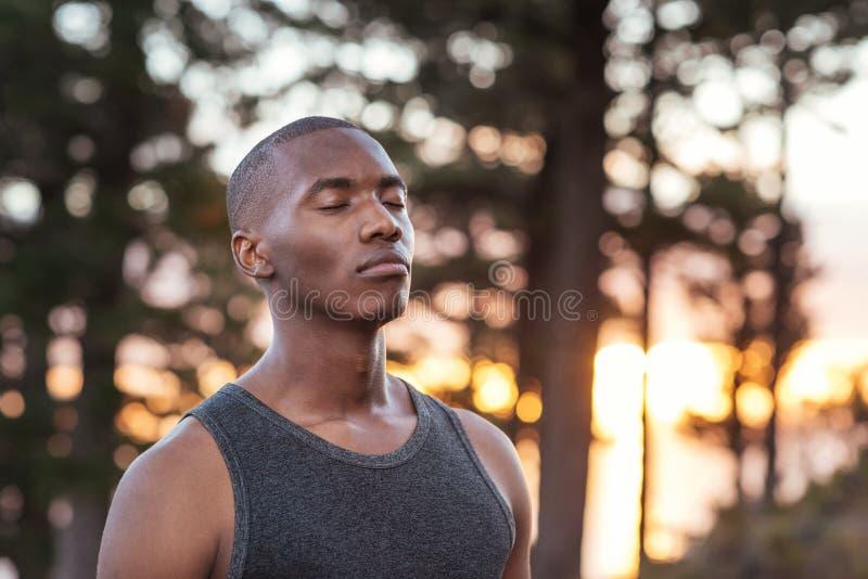 Homem africano novo que obtém focalizado para uma corrida do corta-mato foto de stock royalty free