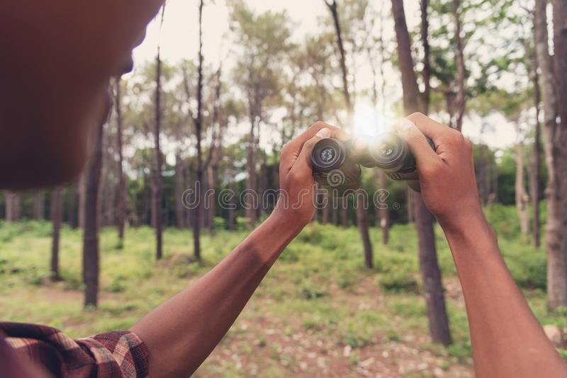 Homem africano novo que olha com binocular na floresta, Trave imagens de stock royalty free