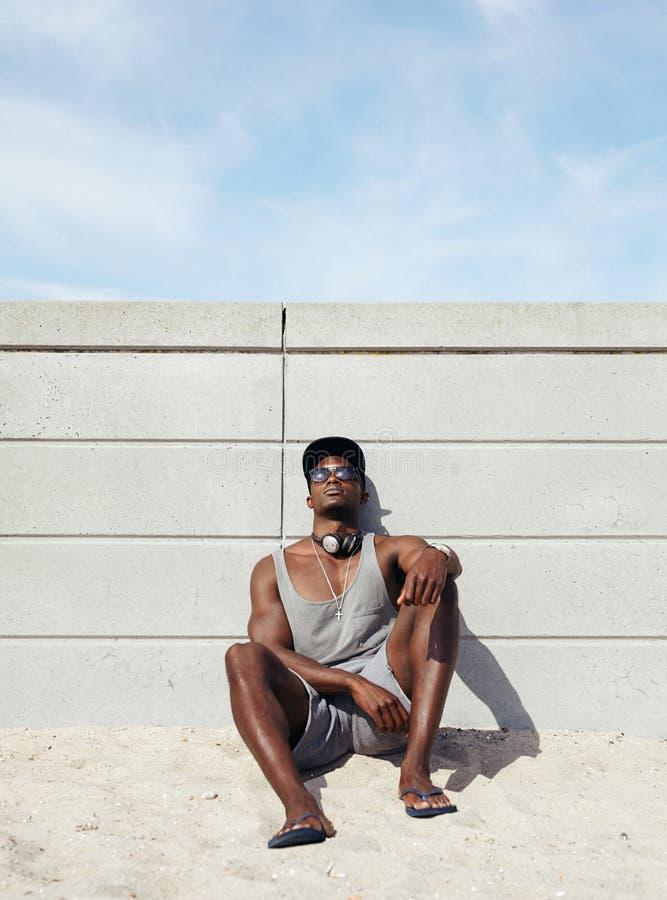 Homem africano novo que relaxa na praia imagem de stock