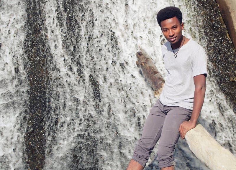 Homem africano novo que senta-se no tronco de árvore na cachoeira do rio imagens de stock royalty free