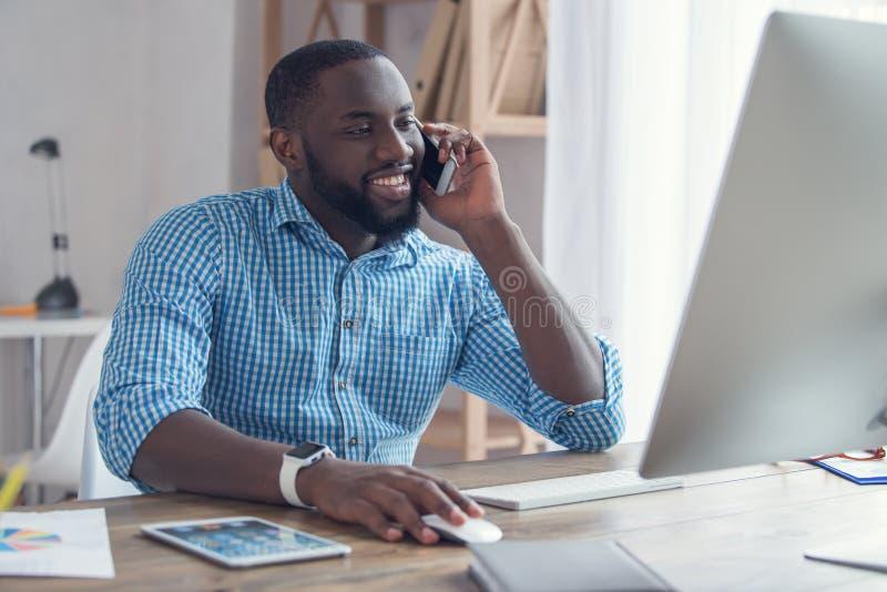 Homem africano novo que trabalha no negócio do escritório imagem de stock