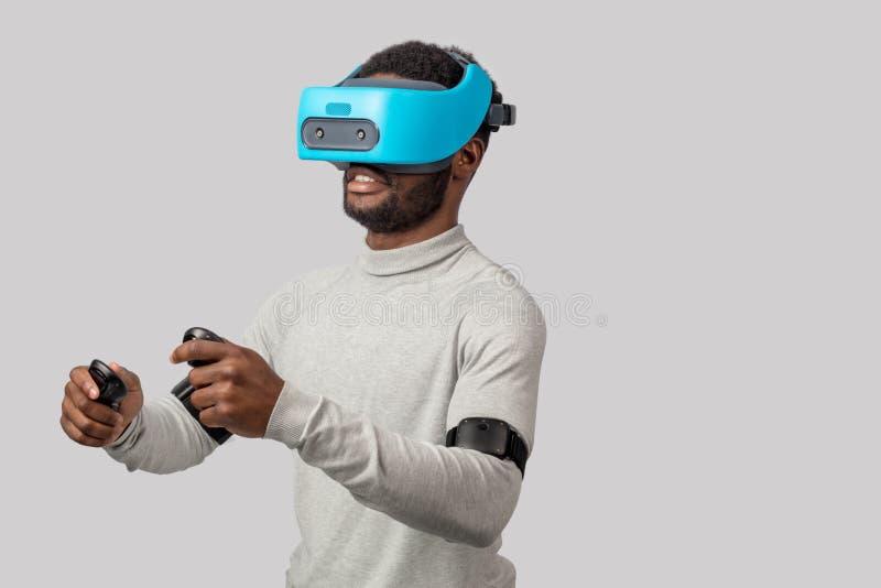 Homem africano novo que veste os óculos de proteção da realidade virtual isolados no fundo branco foto de stock royalty free
