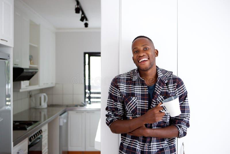 Homem africano novo relaxado que tem uma xícara de café em casa fotografia de stock royalty free
