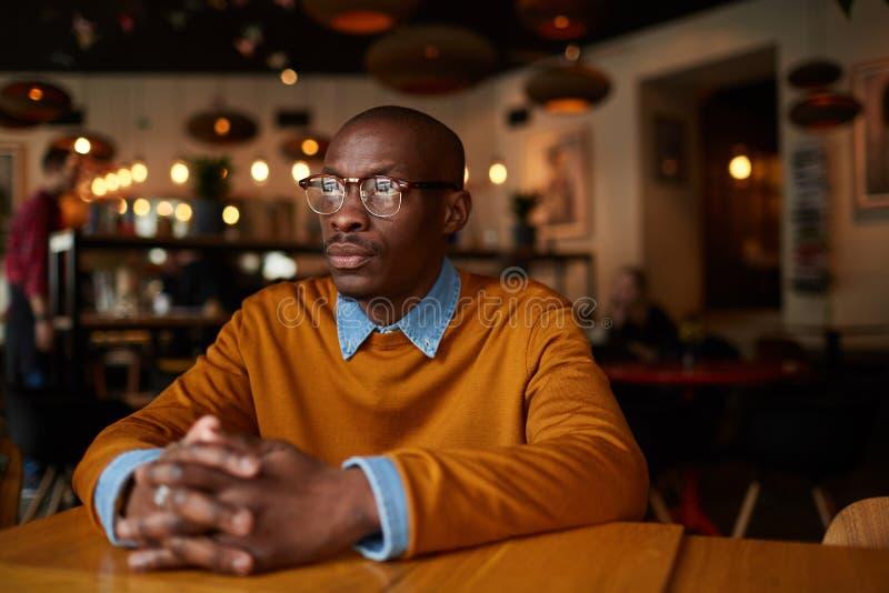Homem africano pensativo no café fotografia de stock royalty free