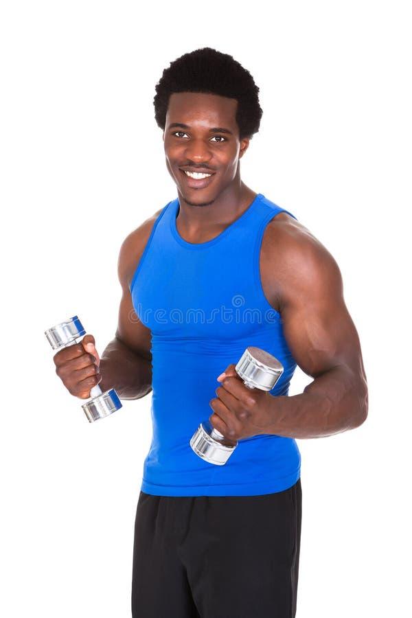 Homem africano que exercita com pesos imagem de stock
