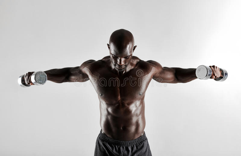 Homem africano que faz o exercício de braços com pesos foto de stock