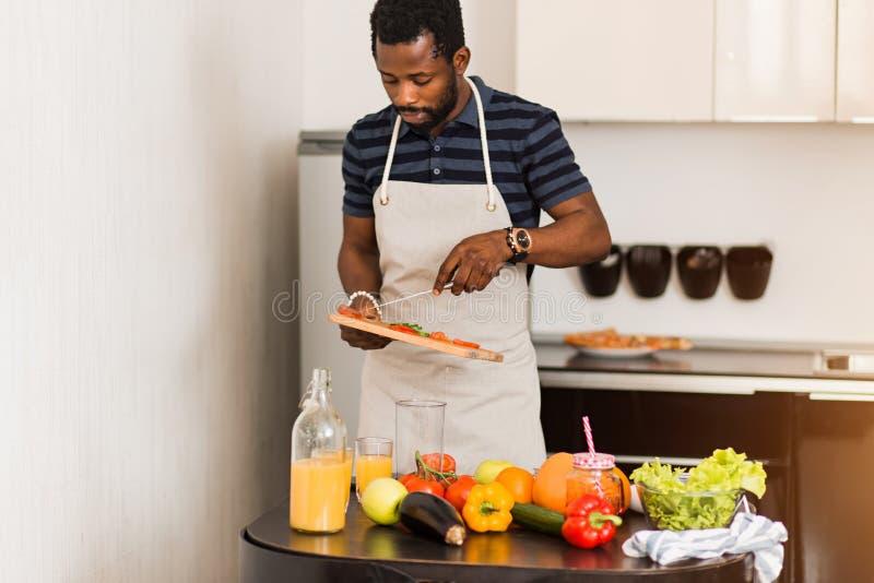 Homem africano que prepara o alimento saudável em casa na cozinha imagem de stock