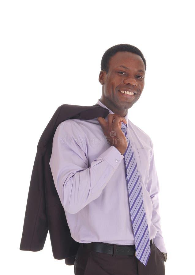 Homem africano que sorri com o revestimento sobre o ombro foto de stock