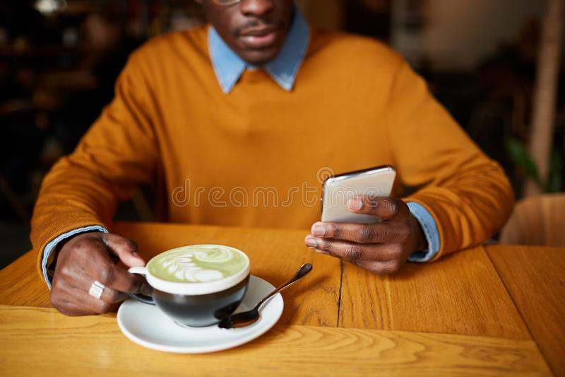 Homem africano que usa Smartphone na cafetaria foto de stock royalty free