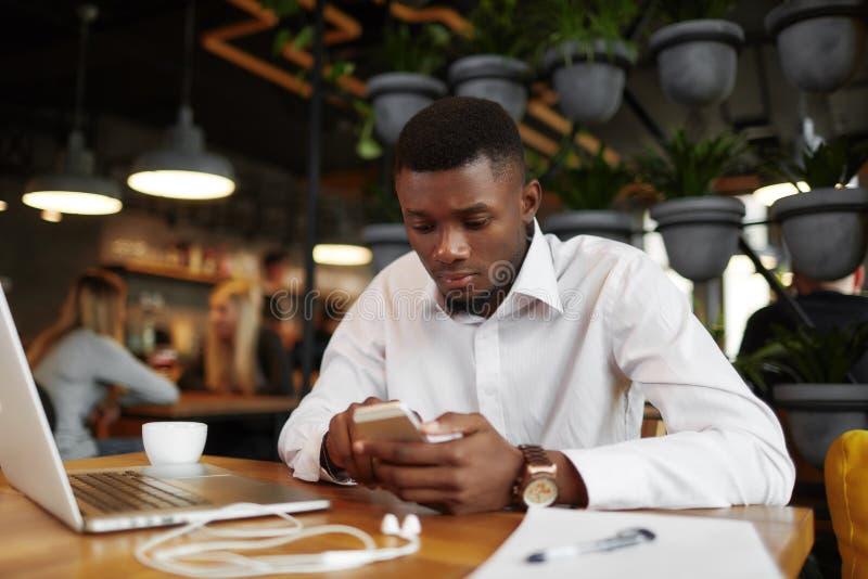 Homem africano sério que conversa, escrevendo a mensagem o telefone esperto imagem de stock royalty free