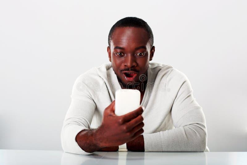 Homem africano surpreendido que senta-se na tabela fotos de stock royalty free