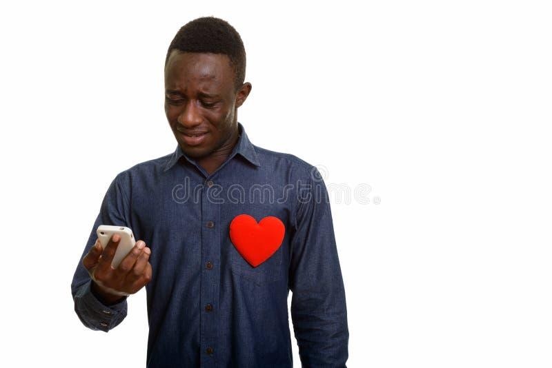Homem africano triste que usa o telefone celular com coração vermelho na caixa fotos de stock