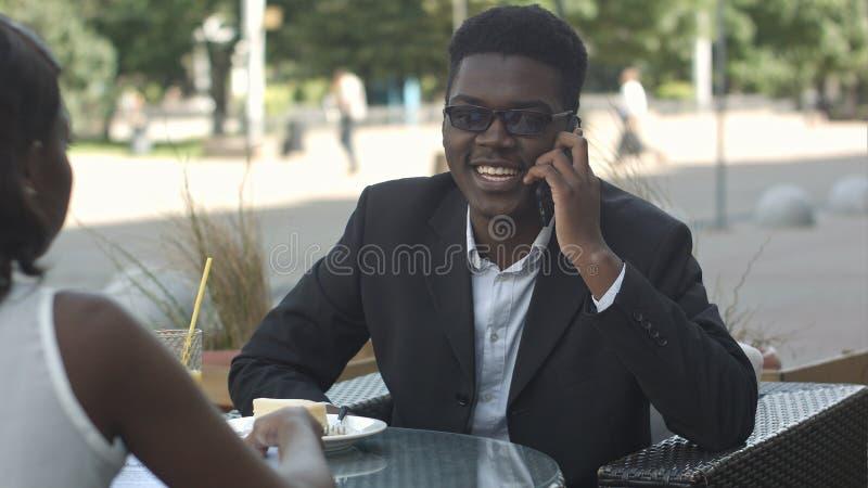 Homem afro-americano agradável que tem o telefonema durante a ruptura de trabalho com seu calleague fotos de stock royalty free