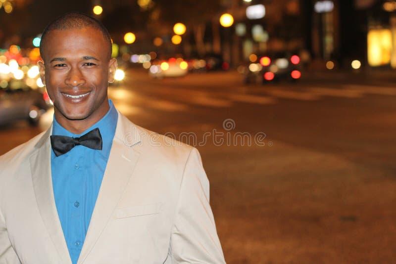 Homem afro-americano agudamente vestido no terno bege na noite na cidade imagem de stock