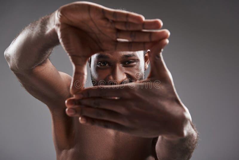 Homem afro-americano alegre que olha o ao gesticular imagem de stock