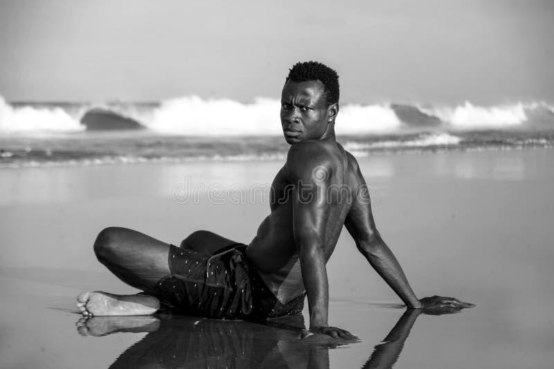 Homem afro-americano atrativo e relaxado novo com corpo apto e a parte traseira muscular que sentam-se na areia da praia que leva foto de stock