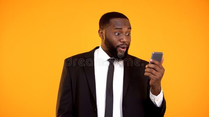 Homem afro-americano chocado no telefone da terra arrendada do terno de neg?cio, recebendo o correio, not?cia imagens de stock royalty free