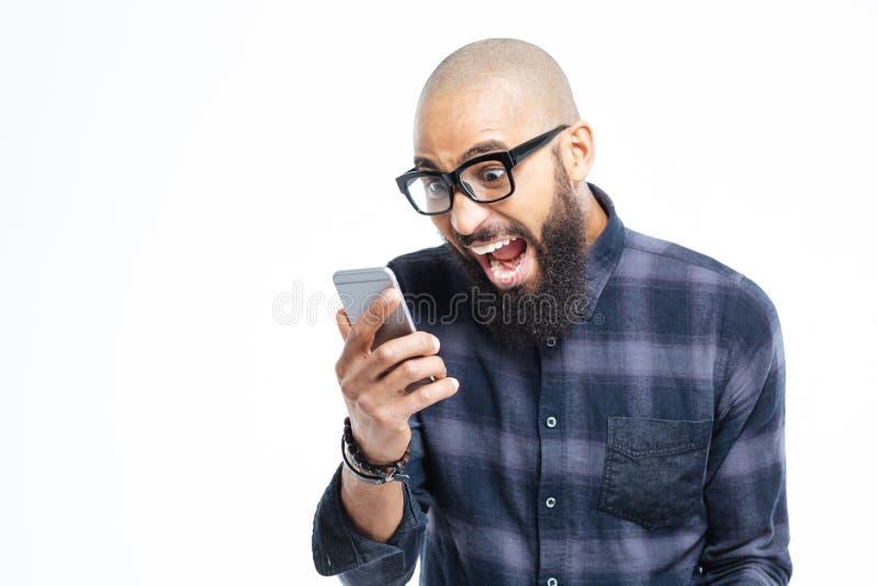 Homem afro-americano chocado que usa o telefone celular e a gritaria imagens de stock royalty free