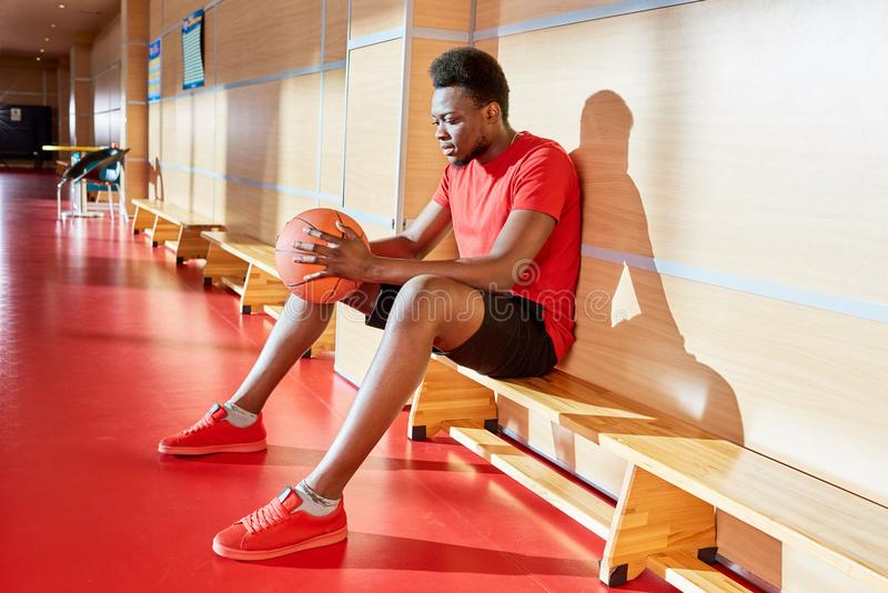 Homem afro-americano com a bola do basquetebol no banco fotografia de stock royalty free